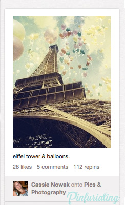 A low angle photo of the eiffel tower with a sepia filter and pastel balloons floating skyward.